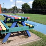 multi coloured bench pictures next to sports field
